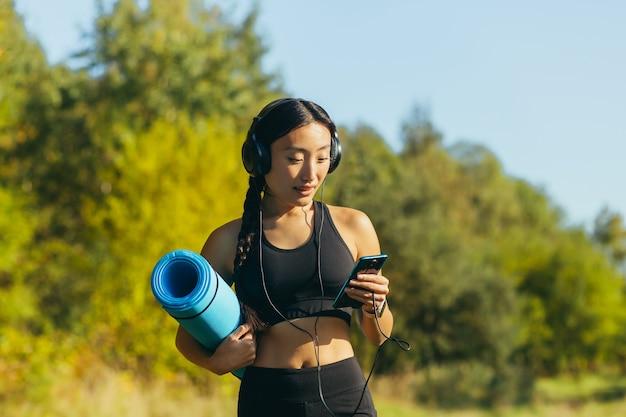 Junge schöne asiatische sportlerin in schwarzen sportanzug-leggings und t-shirt, hört musik in großen kopfhörern mit handy-app, geht zum fitness-workout