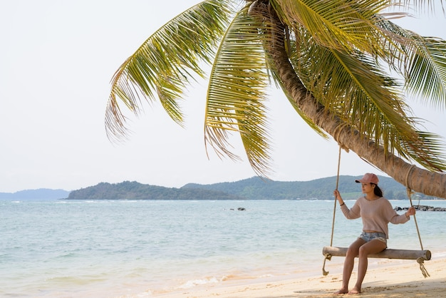 Junge schöne asiatische touristenfrau, die am strand entspannt