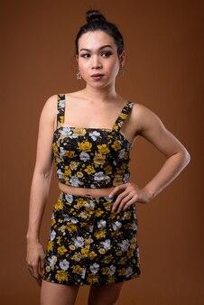 Junge schöne asiatische transgenderfrau gegen braunen hintergrund