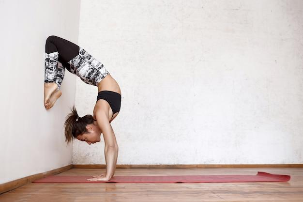 Junge schöne athletische frau, die indoor yoga arm-balance skorpion handstand vrischikasana nahe der wand praktiziert