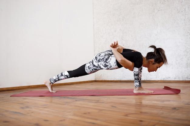 Junge schöne athletische frau, die innenyoga auf roter matte praktiziert