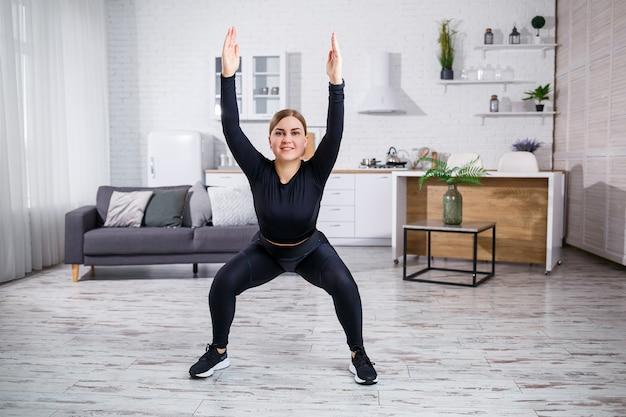 Junge schöne athletische mädchen in leggings und einem top macht dehnübungen. gesunder lebensstil. die frau treibt zu hause sport.