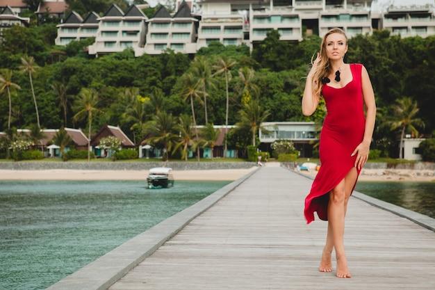 Junge schöne attraktive frau, die allein auf pier im luxusresorthotel, sommerferien, rotes langes kleid, blondes haar, sexy kleidung, tropischer strand, verführerisch, sinnlich, lächelnd steht