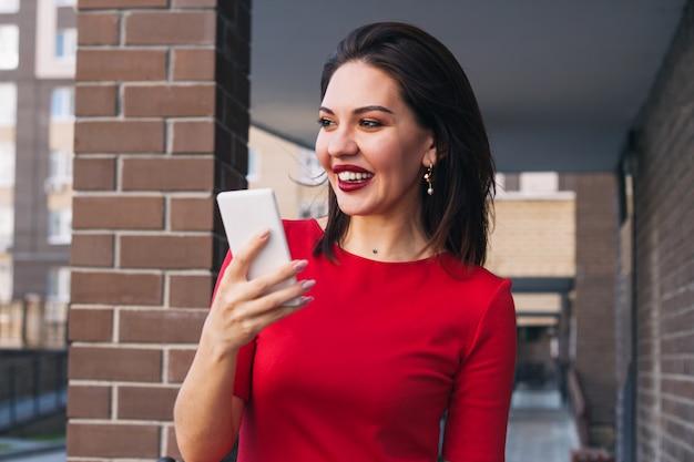 Junge schöne aufgeregte glückliche frau mit rotem lippenstift und tragendem rotem kleid, das draußen handy hält