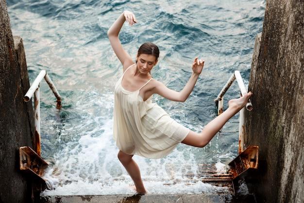 Junge schöne ballerina, die draußen tanzt und posiert