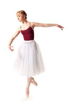 Junge schöne ballerina im weißen tutu und in den spitzenschuhen, die tanzende haltung tun