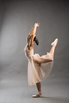 Junge schöne balletttänzerin im beigen badeanzug posiert auf pointes auf hellgrauem studiohintergrund