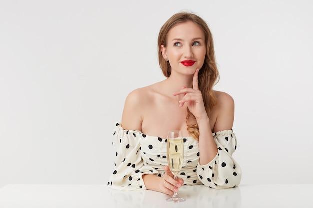 Junge schöne blauäugige frau mit langen blonden haaren und roten lippen, die von neuem kleid träumt. berührt nachdenklich sein kinn mit dem finger und lächelt isoliert über weißem hintergrund.