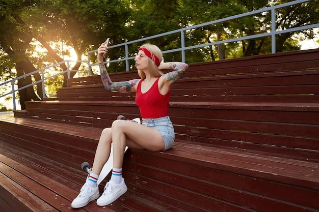 Junge schöne blonde dame mit tätowierten armen in einem roten t-shirt und jeansshorts mit einem gestrickten kopftuch auf dem kopf, in der roten brille, hält smartphone und macht selfie