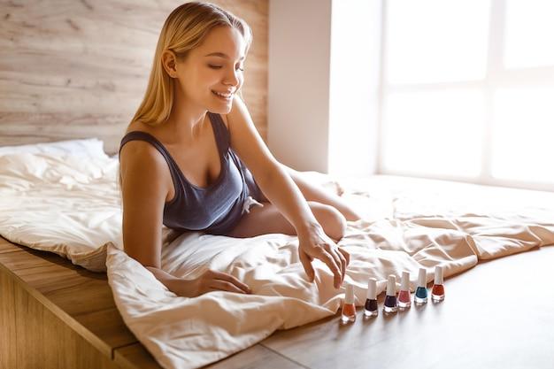 Junge schöne blonde frau, die am morgen im bett sitzt. sie schaut sich bunten nagellack an. sie schaut es sich an und lächelt. sie nimmt farbe auf.