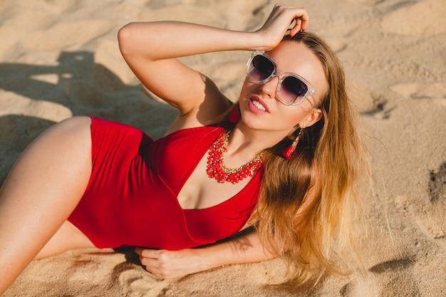 Junge schöne blonde frau, die auf sandstrand im roten badeanzug, sonnenbrille sonnenbad