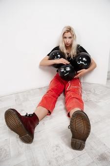 Junge schöne blonde frau, die schwarze ballons hält, die auf boden über weißer wand sitzen