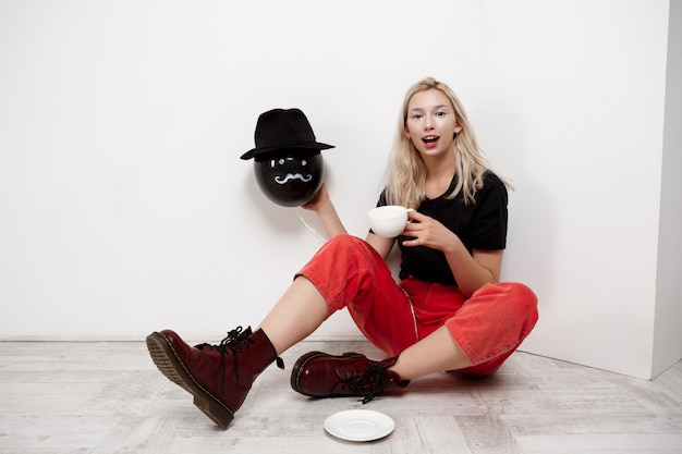 Junge schöne blonde frau, die schwarzen ballon im hut hält, der auf boden trinkt kaffee über weißer wand trinkt