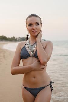 Junge schöne blonde frau, die sich auf sandstrand im bikini-badeanzug, weinlesehalskette sonnt