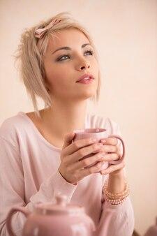 Junge schöne blonde frau, die teeparty hat.