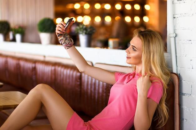 Junge schöne blonde frau im rosa kleid, das fotos von sich selbst macht
