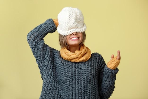 Junge schöne blonde frau im strickmützenpulloverschal und in den fäustlingen, die auf gelb aufwerfen.
