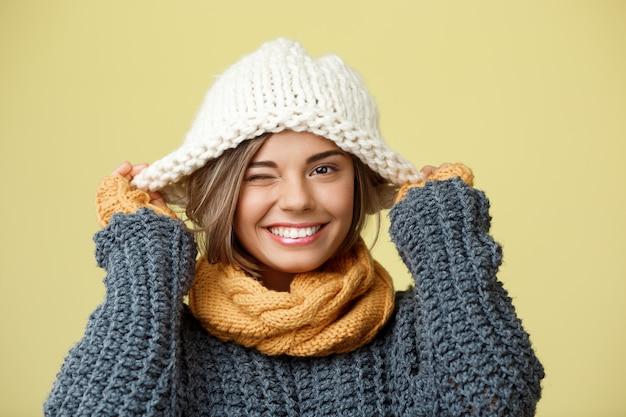 Junge schöne blonde frau im strickmützenpulloverschal und in den fäustlingen, die auf gelb lächeln.