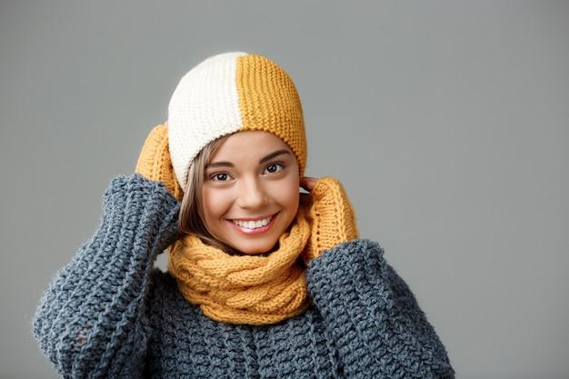 Junge schöne blonde frau im strickmützenpulloverschal und in den handschuhen, die auf grau lächeln.