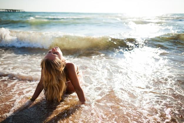 Junge schöne blonde frau im weißen bikini, der am meerwasserrand in den wellen sitzt