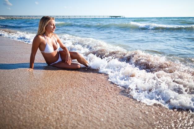 Junge schöne blonde frau im weißen bikini, der am meerwasserrand sitzt und sonnenschein am klaren sommertag genießt