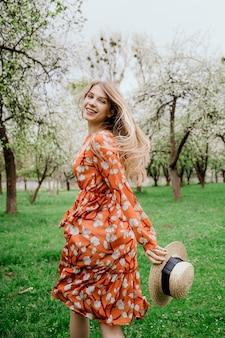 Junge schöne blonde frau in blühendem garten. frühlingsbäume in voller blüte. orange kleid und strohhut.