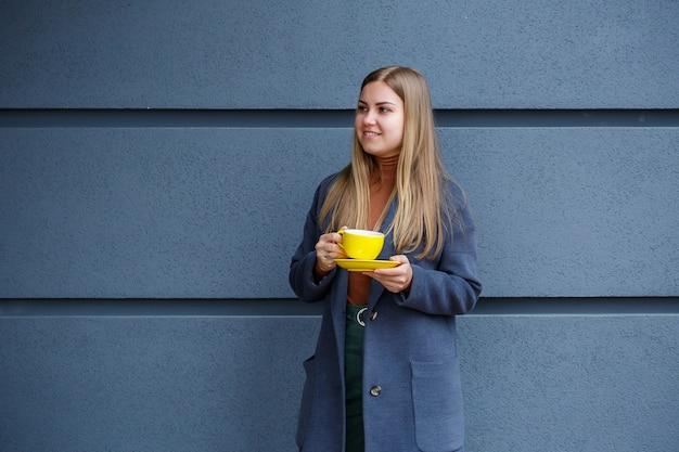 Junge schöne blonde frau in einem grauen mantel trinkt an einem kalten herbsttag heißen tee aus einer gelben tasse. leckeres warmes getränk auf der terrasse im café