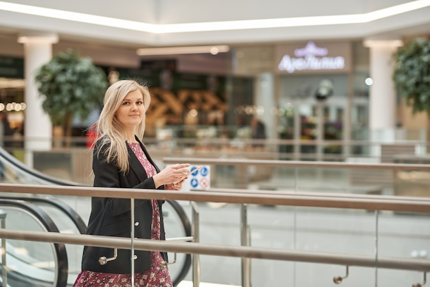 Junge schöne blonde frau in einem kleid auf einer rolltreppe in einem einkaufszentrum, mit einem telefon in ihren händen
