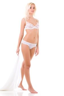 Junge schöne blonde frau in weißen dessous über weißem hintergrund im fotostudio. schönheit des frauenkörperkonzepts