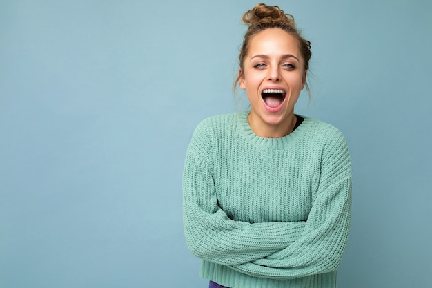 Junge schöne blonde frau mit blauem pullover, die kamera positiv anschaut, zeigt gesichtsbehandlungen