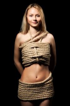 Junge schöne blonde frau mit körper bedeckt mit seilen, die kamera über schwarzem hintergrund bleiben und betrachten. sexuelle spiele und praktizierendes bdsm-konzept