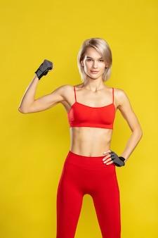 Junge schöne blonde frau mit starken armen in roter sportkleidung, die ihren bizeps zeigt und in die kamera schaut