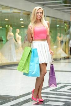Junge schöne blonde frau mit taschen zum einkaufen.
