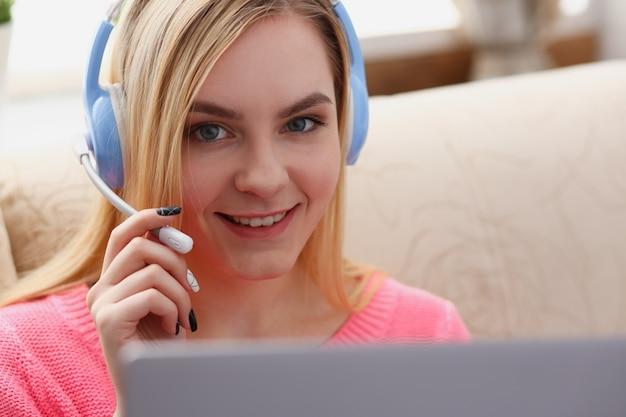 Junge schöne blonde frau sitzen auf dem sofa im wohnzimmer halten laptop in den armen hören musik
