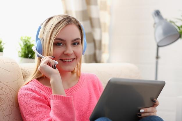 Junge schöne blonde frau sitzen auf dem sofa im wohnzimmer halten tablette in den armen hören musik sonnig