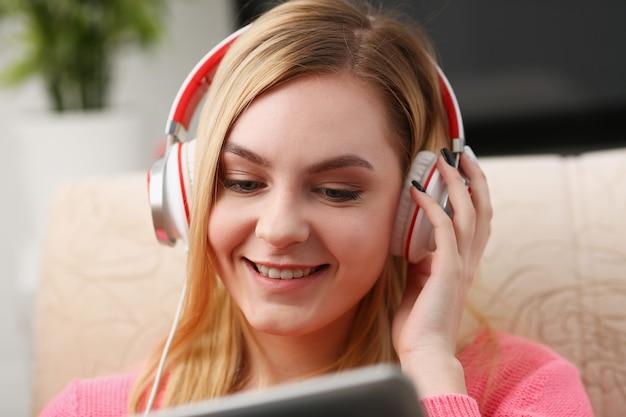 Junge schöne blonde frau sitzen auf dem sofa im wohnzimmer halten tablette in den armen hören musik sonnigen morgen konzept