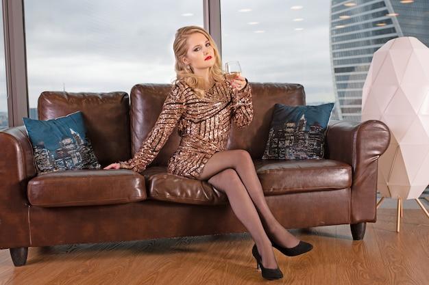 Junge schöne blonde frau sitzt auf einem ledersofa mit einem glas champagner vor dem hintergrund eines panoramafensters mit blick auf die wolkenkratzer und eine große stadt.