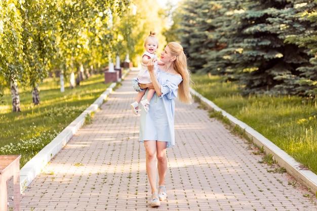 Junge schöne blonde mutter mit ihrem baby, das zusammen lacht