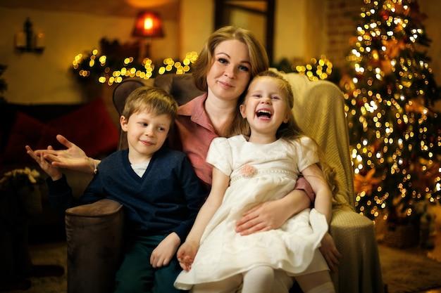 Junge schöne blonde mutter mit zwei kindern posiert im sessel im weihnachtsinterieur