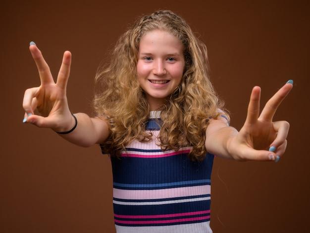 Junge schöne blonde teenager-mädchen lächelnd und friedenszeichen geste machen