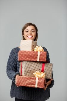 Junge schöne blondhaarige frau im gestrickten pullover lächelnd, die geschenkboxen auf grau hält.