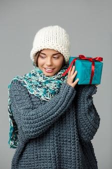 Junge schöne blondhaarige frau im strickmützenpullover und im lächelnden schal, die geschenkbox auf grau halten.