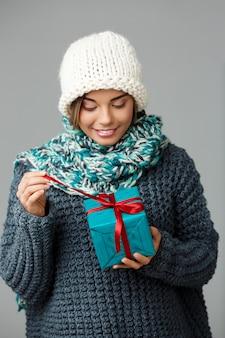 Junge schöne blondhaarige frau im strickmützenpullover und im schälenden lächelnden eröffnungsgeschenkbox auf grau.