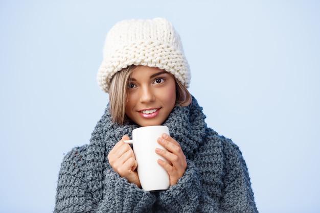 Junge schöne blondhaarige frau in der strickmütze und im pullover halten tasse, die auf blau lächelt.