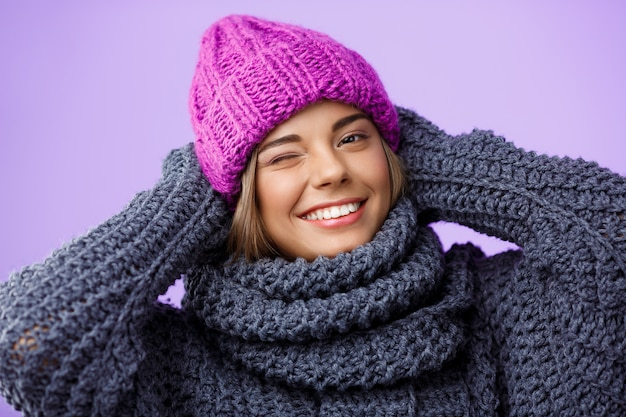 Junge schöne blondhaarige frau in der strickmütze und im pullover lächelnd, die auf veilchen zwinkert.