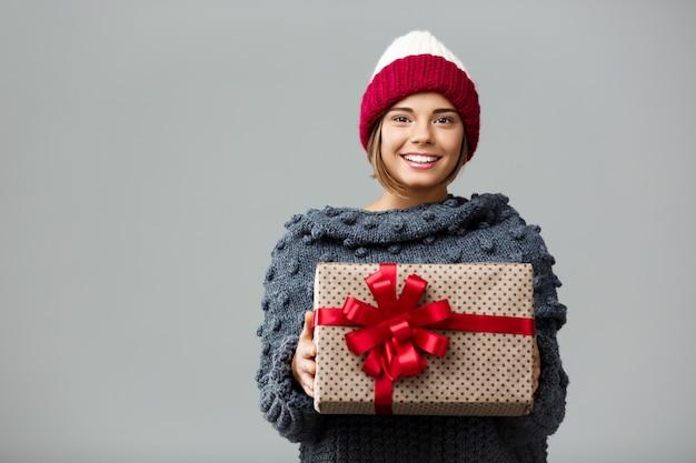Junge schöne blondhaarige frau in der strickmütze und im pullover lächelnd, die geschenkbox auf grau hält.