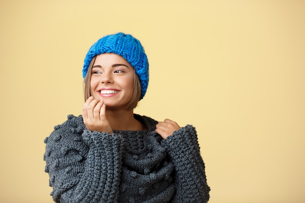 Junge schöne blondhaarige frau in der strickmütze und im pullover lächelnd, die seite auf gelb schauend.