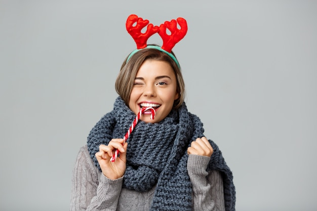 Junge schöne blondhaarige frau in großem gestricktem schal und weihnachtlichem rentiergeweih lächelnd, das gestreiften lollypop auf grau isst.
