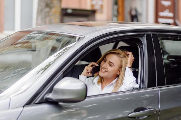 Junge schöne blondine im auto mit telefon