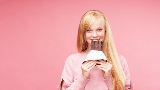 Junge schöne blondine mit schokolade.